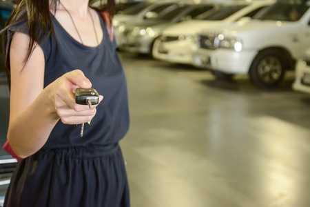Woman unlocking car with car fob