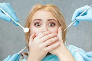 A woman covering her mouth as gloved hands that are holding dentist tools reach out to her