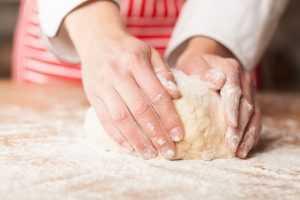 Woman's hand focused on kneading dough