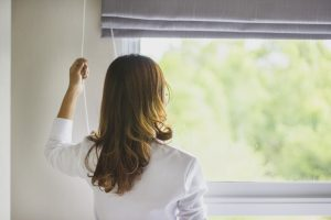 Woman looking to the nature around her through a glass window