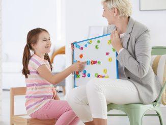 Teacher Helping a Young Girl with Her Speech Problem