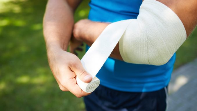 Man bandaging his injured arm