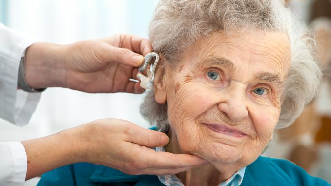 Old Woman Being Fitted With Hearing Aid