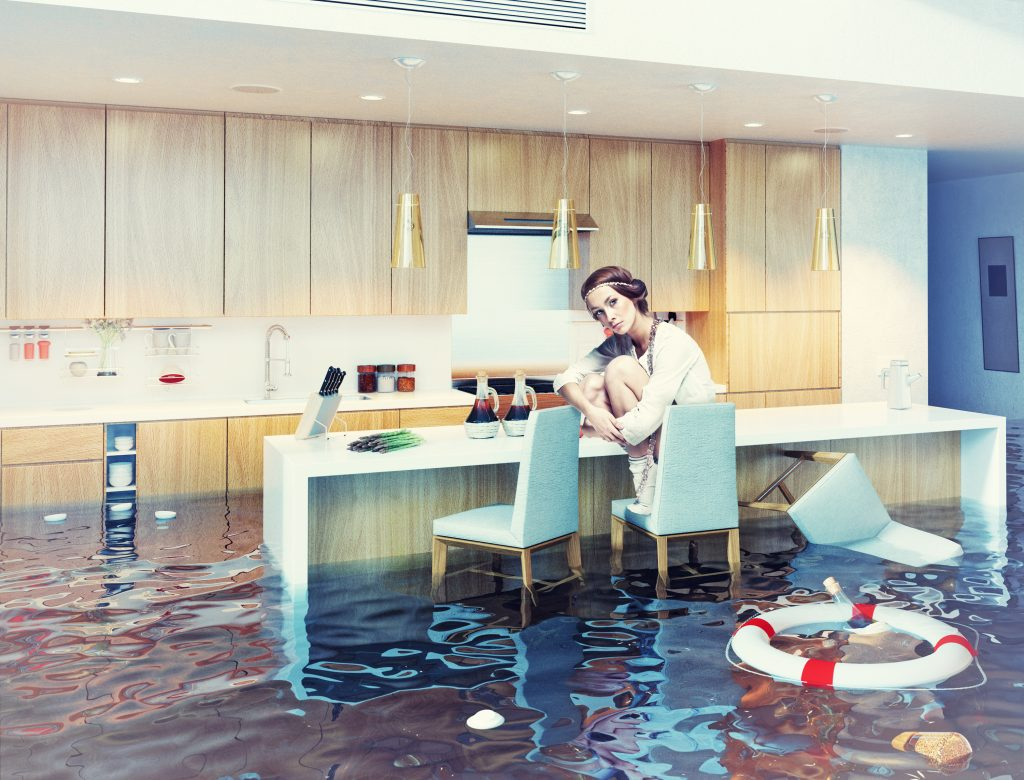 A woman sitting in a flooded kitchen