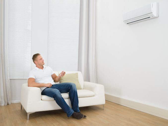 A man adjusting the settings on his AC