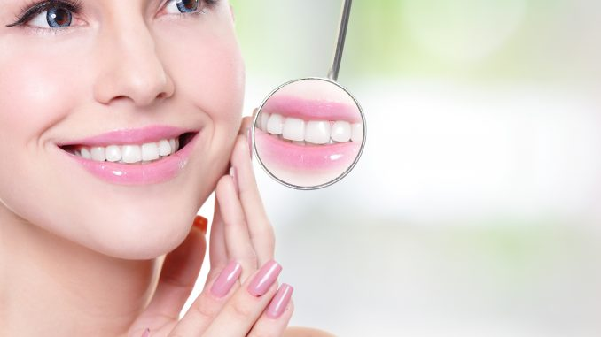 a woman white teeth reflected on a dental mirror