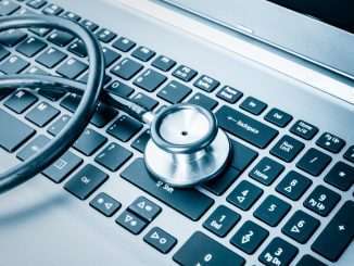 Stethoscope over a computer keyboard toned in blue