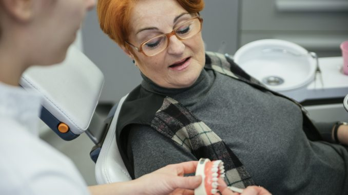 Dentist showing patient's dentures