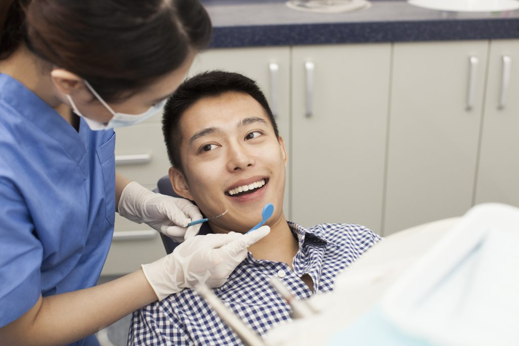 Man being checked by a dentist