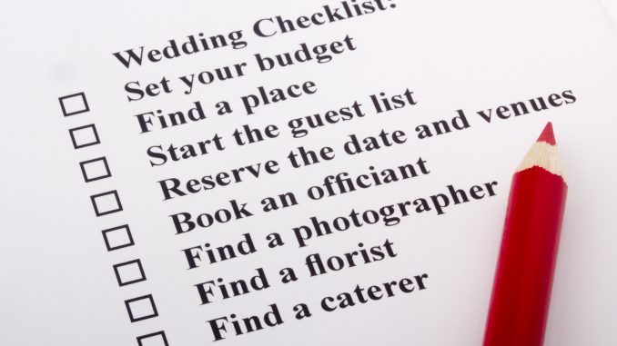 Red pencil laying on a wedding checklist