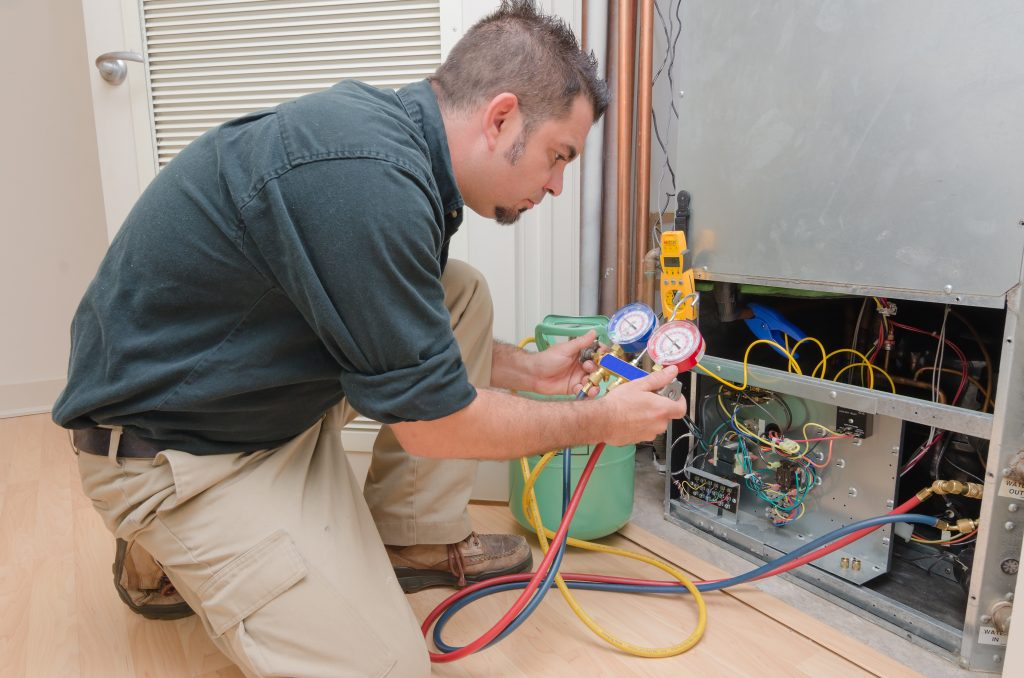 a HVAC technician charging a heat pump