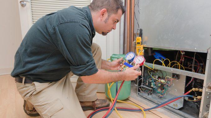 a HVAC technician charging a heat pump