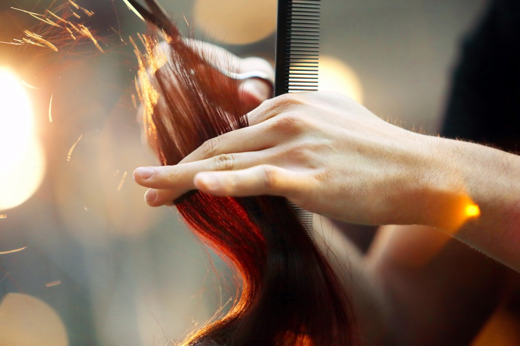 Hairdresser cutting brown hair