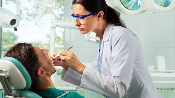 Man being checked by dentists