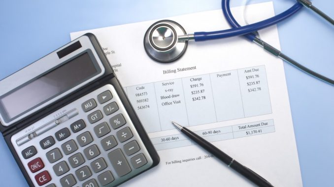 Medical Billing Statement Under A Calculator, A Pen and A Stethoscope