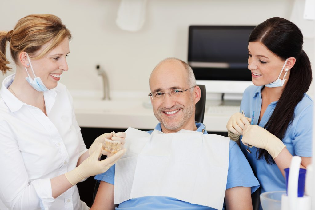 Man being checked by two dentists