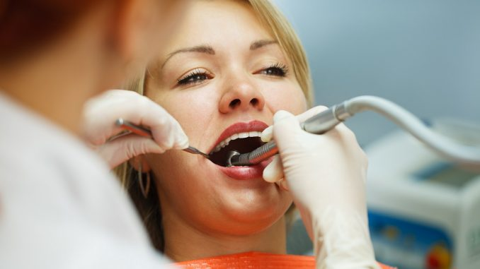 dentist giving the female patient her dental treatment