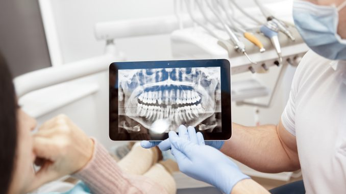 Dentist explaining area of surgery using an x-ray