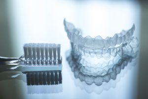 invisalign aligners and a toothbrush