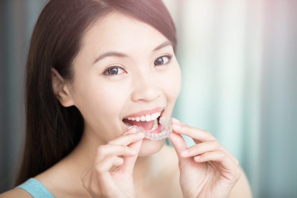woman putting on invisible braces