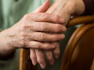 elderly person holding both her hands