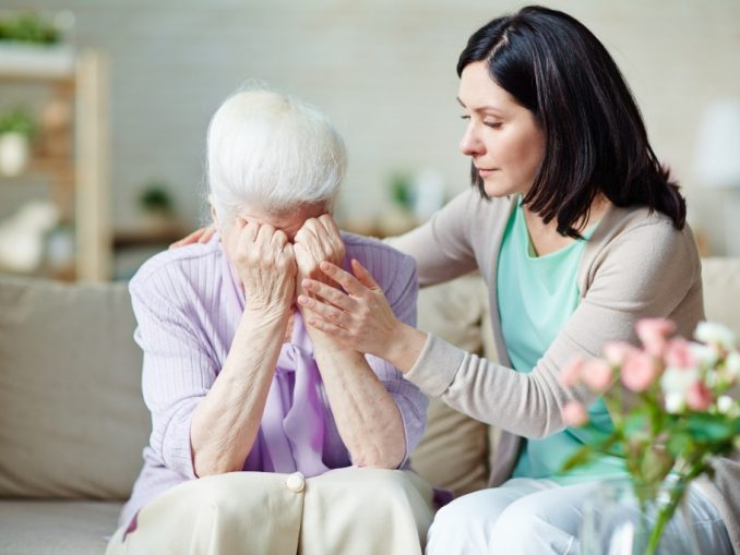 elderly woman is crying while being comforted by her carer
