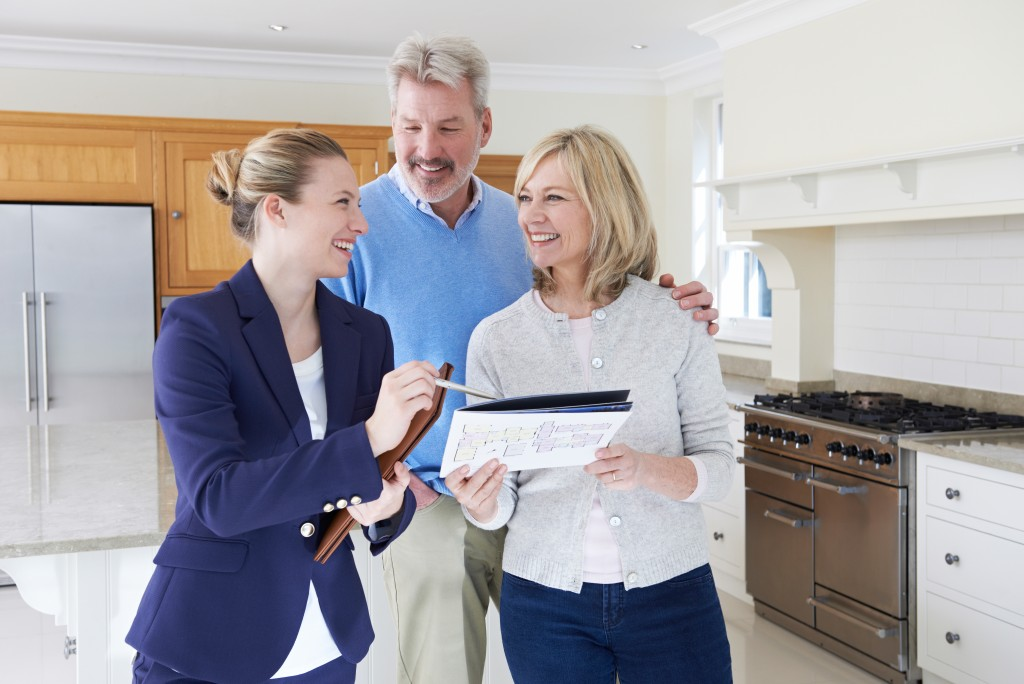 Broker touring a middle-aged couple around a house