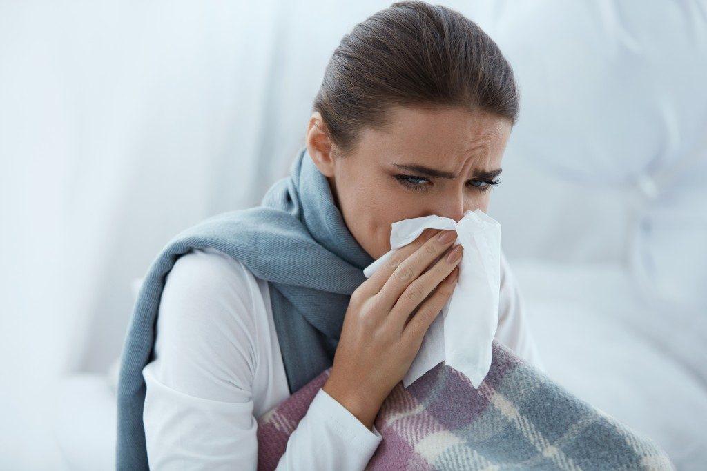 Ill woman sneezing