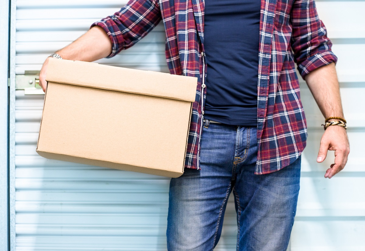 Man in plaid holding a box