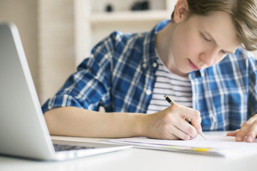 Man in plaid writing an essay