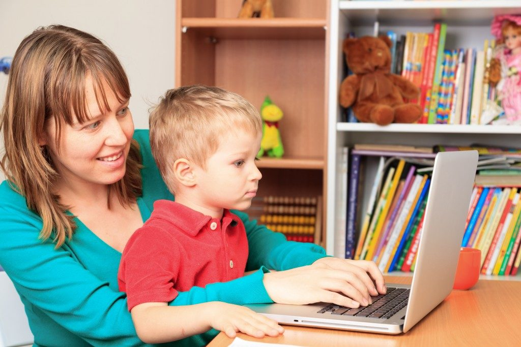 woman teaching a child on how to read online