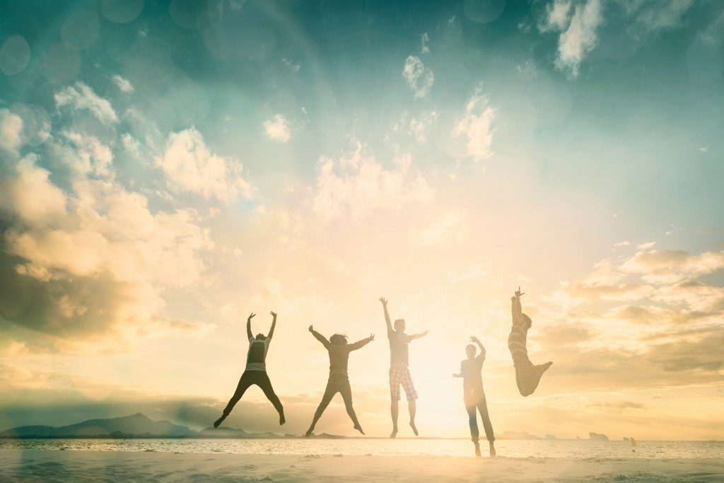 Teens jumping with sunrise background