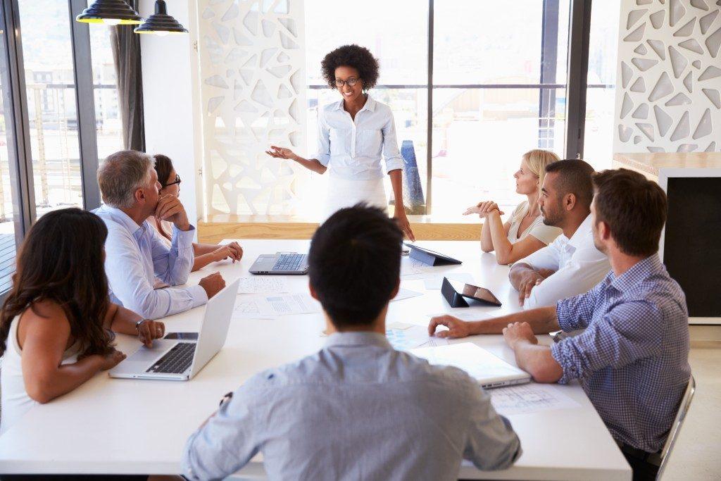employees listening as a woman speaks