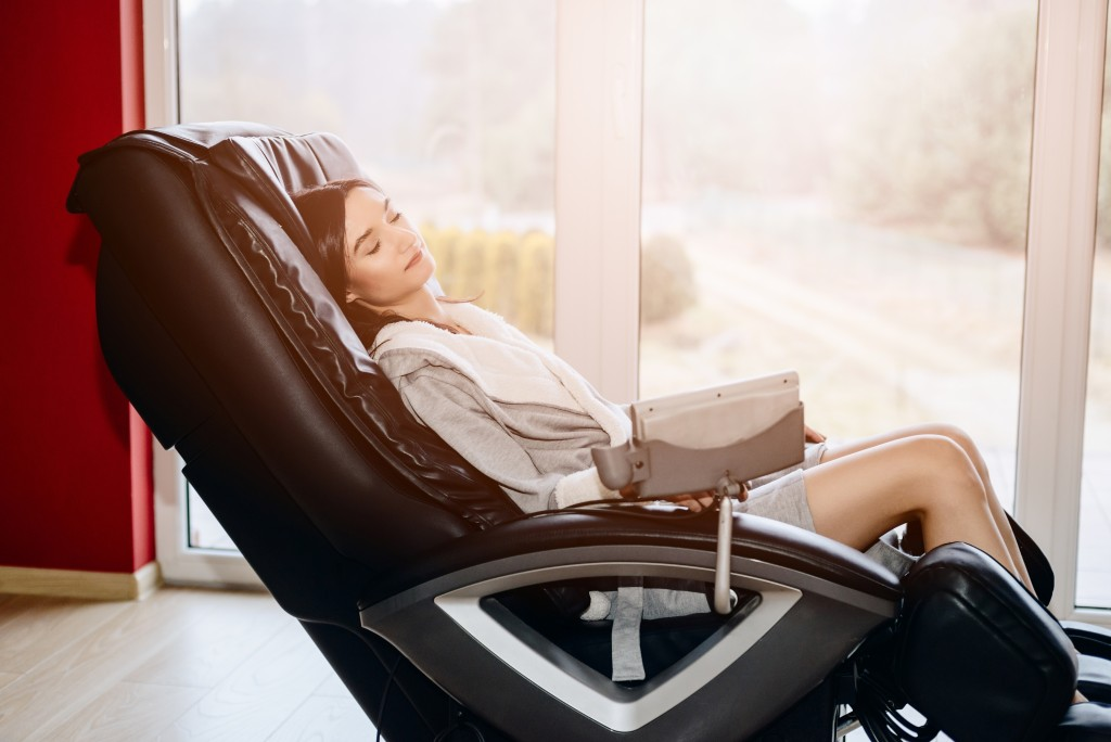 woman relaxing on the massaging chair at home