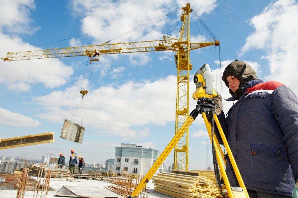 man surveying land next to crane