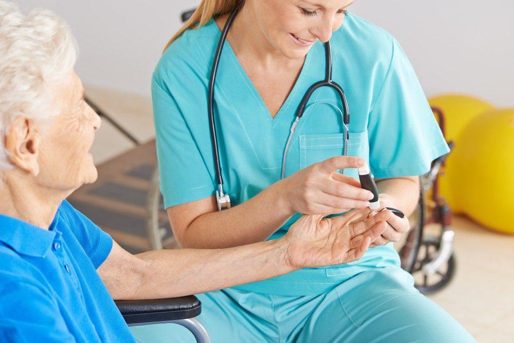 Female nurse monitoring the senior's blood sugar