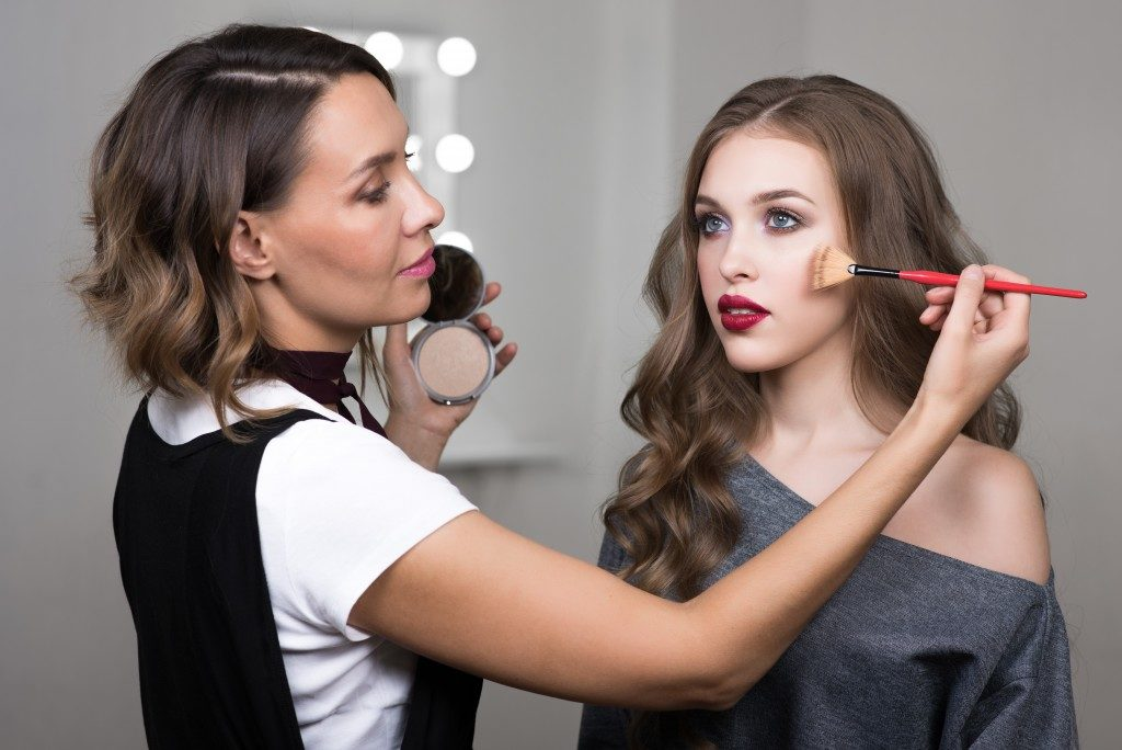 Make up artist doing makeup on the model