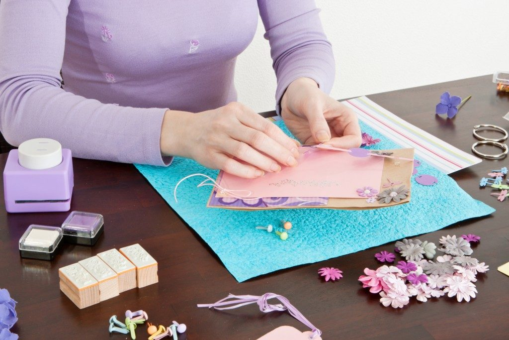 woman wrapping gifts and adding handcrafted designs