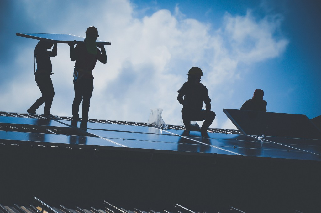 Workers intalling solar panels on the roof