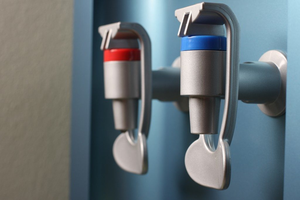 closeup of hot and cold faucet of water dispenser