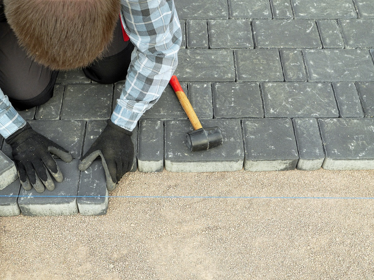 Worker laying pavement blocks