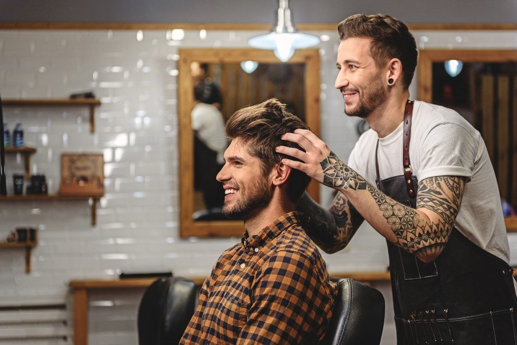 barber styling hair of handsome guy