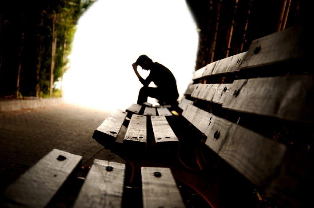 Man-sitting-on-bench-alone