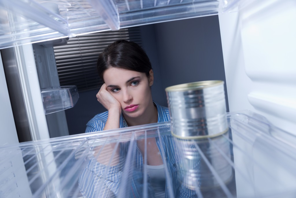 sad woman looking at empty freezer