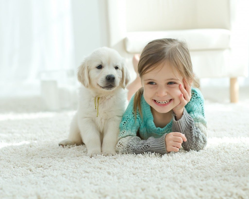 child with the dog lying on the mat at home