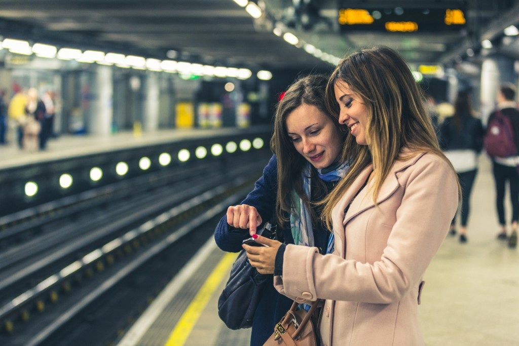 two women looking at the phone in a subway