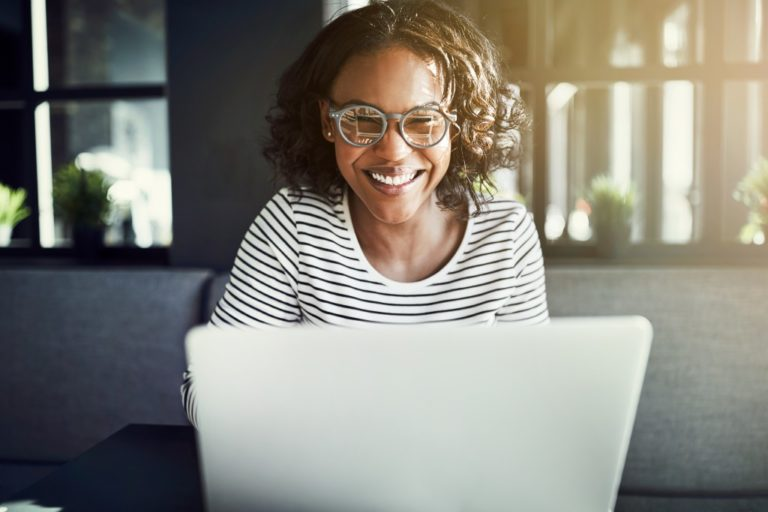 woman smiling at her laptop