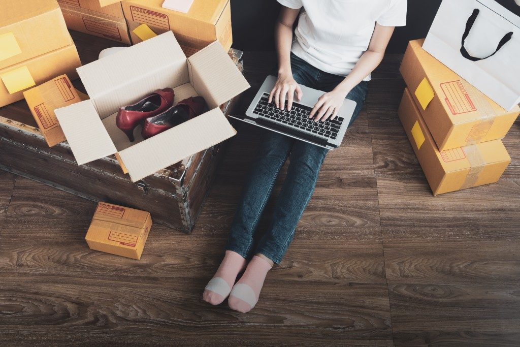 Woman using laptop while sitting on floor beside boxes