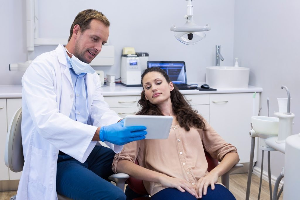 dentist showing information to his patient