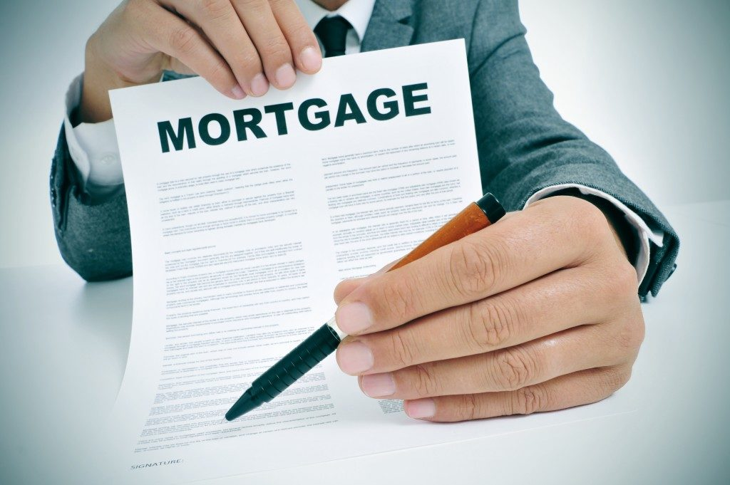 Businessman holding a mortgage contract